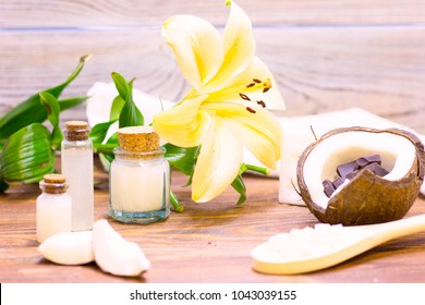 Natural herbal skin care products, top view ingredients coconut, lily flower, essence oil on table concept of the best all natural face moisturizer. Facial treatment preparation background