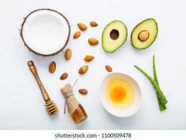 Natural herbal skin care products, top view ingredients coconut,almond, aloe vera, avocado,egg,honey on table concept of the best all natural face moisturizer. Facial treatment preparation background.