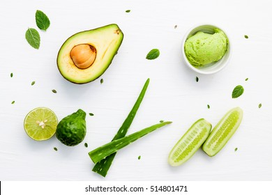 Natural herbal skin care products, top view ingredients. Cosmetic, soap, sea salt, herbs, mint leaf, cucumber, aloe vera, avocado. Facial treatment preparation background.