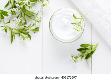 Natural herbal spa cosmetic hygienic cream with flowers skincare product in glass jar on white background