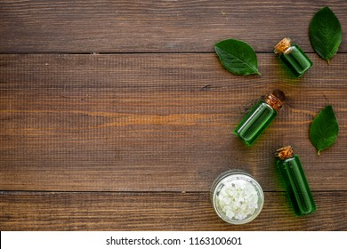 Natural hipoallergenic cosmetics with tea tree essential oil. Oil, lotion, leaves on dark wooden background top view copy space
