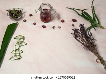 Natural home skin care. Ingredients for the lotion. Leaves and pieces of aloe Vera, rose water, dried rose and sage inflorescences on a background of pink marble. Free space.