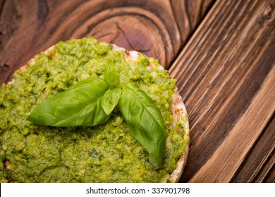 Natural homemade DIY vegan very healthy green pesto made of radish leaves and nutritional yeast flakes on a rice waffle with basil in a glass jar on a wooden table