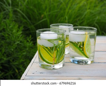 Natural homemade repellent on white wooden table. Slice of lime and lemon, tea light candles, fresh rosemary and water in three glasses.