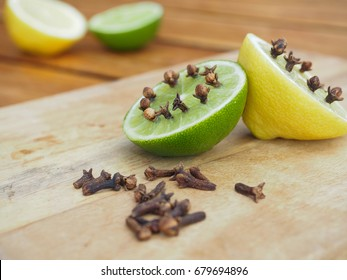 Natural homemade repellents on wooden table. Lime and lemon with cloves.