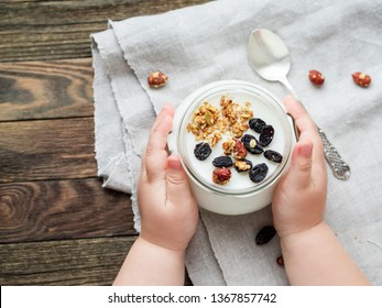 Natural homemade yogurt in a glass jar. Healthy food for breakfast in child's hands. Kid holding jar with muesli on linen tablecloth on on wooden table.
