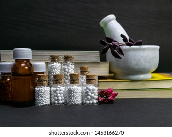 Natural Homeopathy Concept – Healing herbs in a mortar and pestle next to homeopathic medicine consisting a bottle of pills- books and liquid homeopathic substance dark background