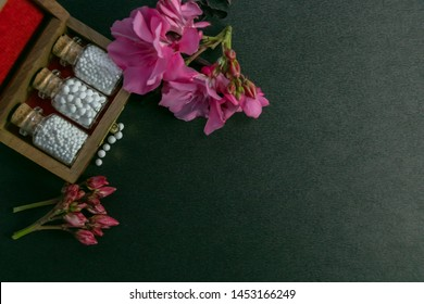 Natural homeopathy - Top view of homeopathy medicine bottles in wooden old box with pink flowers and some scattered globules on dark background