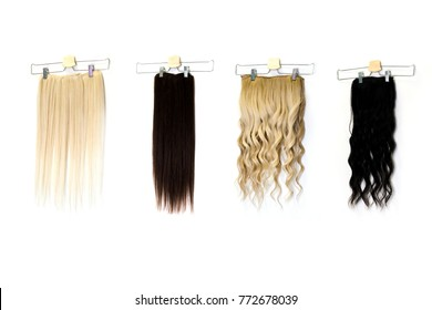 Natural human hair extensions hung on a white wall in the beauty salon, space for text. Multicolor straight and curly tape in colorful remy human hair extensions.