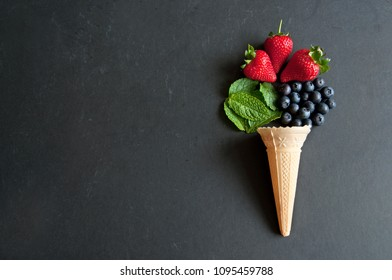Natural ingredients spilling out of an icecream cone including strawberry, mint and blueberries
