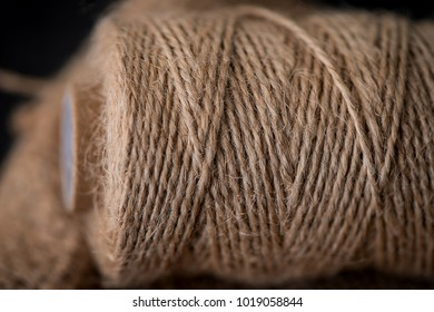 Natural jute twine roll, burlap on black background. Supplies and tools for handmade hobby leisure closeup