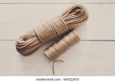 Natural Jute Twine Roll, top view on white wood background. DIY Wrap Gift Hemp Rope Cord String Roll, supplies and tools for handmade hobby leisure