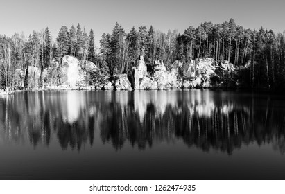 Natural lake in Adrspach rocks on sunny autumn day. Adrspach-Teplice sandstone rock town, Czech Republic. Black and white image.