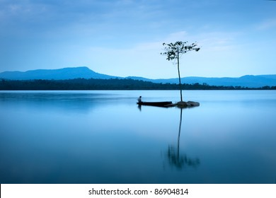 Natural landscape in blue. A boat floating in smooth water at tranquil lake .Many traveller come for relaxing after hard working. This a beautiful gift from the nature