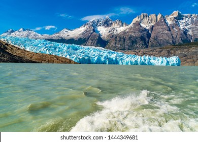 Natural landscape at Glacier Grey with the snowy rock mountain, Lake Grey and water splash behind the ship at Torres del Paine National Park in Chile