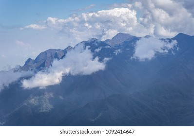Natural landscape of high mountain in Brazil with clouds near the peaks.