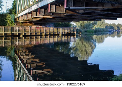 Natural landscape of reflections in water of the River Cam under the railway bridge in East Chesterton, Cambridge. With wooden walkway into countryside beyond.