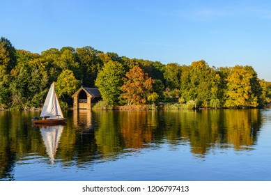 Natural landscape view of forest with autumn leaves in Pfaueninsel island and boat sail at Wannsee lake,  Havel river from colour changed grassland on waterside of Westlicher Düppeler forest, Berlin.