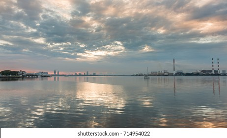 natural landscapes. blue clouds that make up the original abstract. there is a building in the background. there is a small boat in the water and a reflection of light