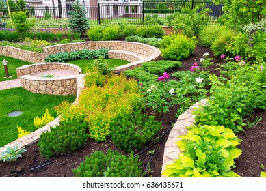 Natural landscaping with decorative stone in home backyard. Beautiful landscaping with flowerbed in summer. Landscaped flower garden.