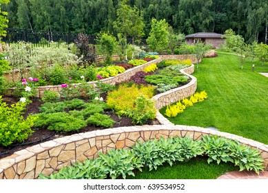 Natural landscaping panorama in home garden. Beautiful view of nice landscaped garden in backyard. Scenery of landscaping area in summer. Landscape design with flower beds.