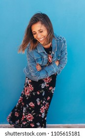 Natural laughing trendy young woman in a denim jacket and floral dress bending forwards with a happy smile isolated on blue