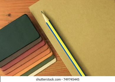 Natural leather samples variety shades of colors with notebook and pencil on wood table, designer concept.