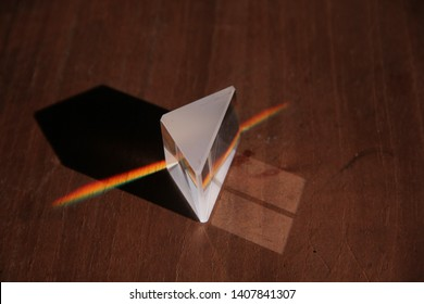 natural light focuses on the optical prism, refracting a color spectrum  under a wooden table.