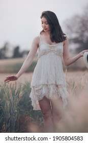 natural light portrait beautiful asian women girl in a while wedding dress and hut for walk relax on the agriculture barley rice fields at chiang mai Thailand, alone nature people concept vintage styl - Shutterstock ID 1905804583