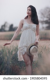 natural light portrait beautiful asian women girl in a while wedding dress and hut for walk relax on the agriculture barley rice fields at chiang mai Thailand, alone nature people concept vintage styl - Shutterstock ID 1905804595