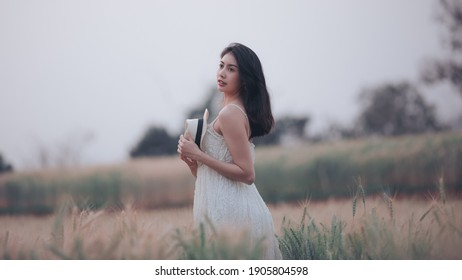 natural light portrait beautiful asian women girl in a while wedding dress and hut for walk relax on the agriculture barley rice fields at chiang mai Thailand, alone nature people concept vintage styl - Shutterstock ID 1905804598