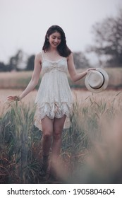 natural light portrait beautiful asian women girl in a while wedding dress and hut for walk relax on the agriculture barley rice fields at chiang mai Thailand, alone nature people concept vintage styl - Shutterstock ID 1905804604