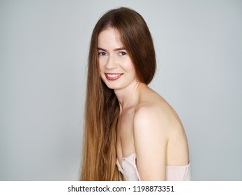 Natural light portrait of young beautiful blond woman with long hair in vintage dress smiling looking at camera over grey wall background.