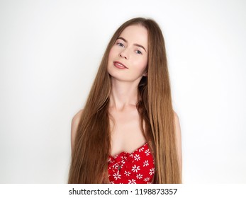 Natural light portrait of young beautiful blond woman with long hair in vintage red dress smiling looking at camera over white wall background.