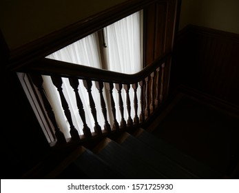 Natural light streaming through the curtains by a flight of stairs at an old mansion