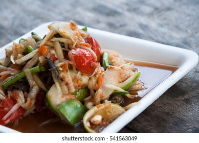 Natural lighting and shadow of blur Papaya Spicy Salad with Salted Crab and Fermented Fish served in foam plate on dining table of restaurant in Chiang Dao, Chiang Mai, Thailand