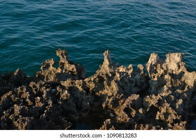 Natural limestone formations highlighted by sun in Bali ahead of a sea water background.