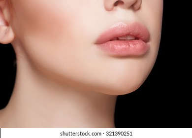 Natural lips. Close up shoot in studio on black