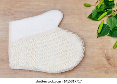 Natural loofah glove and birch green leaves, flat lay, top view. Eco bathroom accessories, cosmetics products, plastic free. Organic vegan body care and facial care, Sisal Fiber Sponge