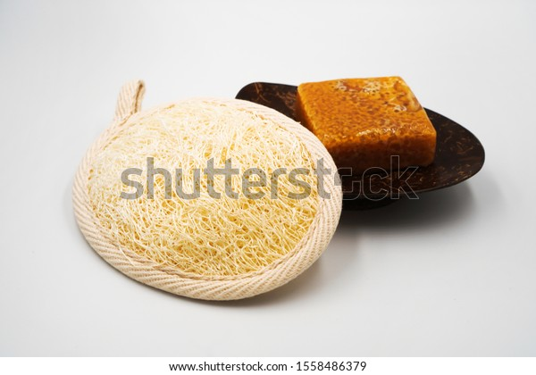Natural Loofah or Luffa Sponge pad for Face and Body Bath Exfoliate and coconut shell soap dish or holder with natural handmade honey soap ,as set of bathroom accessory ,isolated on white background