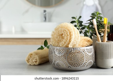 Natural loofah sponges and toothbrushes on table in bathroom. Space for text