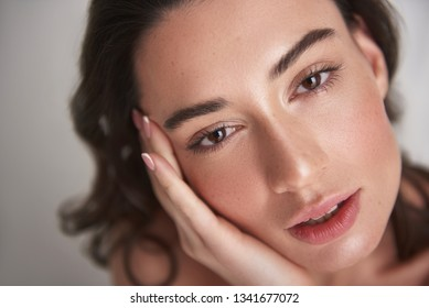 Natural look. Close up portrait of young sensual brunette female with enigmatic glance looking straight on camera while laying her face on palm. Isolated on white