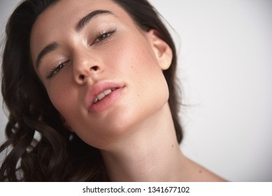 Natural look. Close up portrait of young sensual brunette lady with careful soft skin and enigmatic glance looking straight on camera. Isolated on white