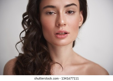 Natural look. Close up portrait of young naked sexy brunette lady with careful soft skin and enigmatic glance looking straight on camera. Isolated on white