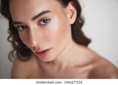 Natural look. Close up portrait of young naked brunette pretty lady with careful soft skin and enigmatic glance looking straight on camera. Isolated on white