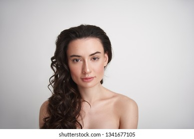 Natural look. Portrait of young naked sexy brunette lady with curly hairs and enigmatic glance looking straight on camera. Isolated on white