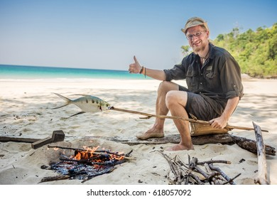 Natural looking man baking a fish on open fire on the white beach, Southeast Asia