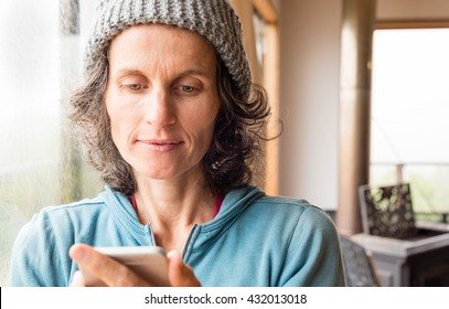 Natural looking mature woman in grey knitted hat using smart phone with woodstove in background (selective focus)