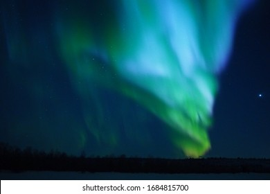 Natural looking multicolored green and blue aurora borealis (northen lights) with Venus in the border of Finland and Norway