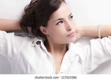 natural looking young woman portrait in white linen shirt studio shot